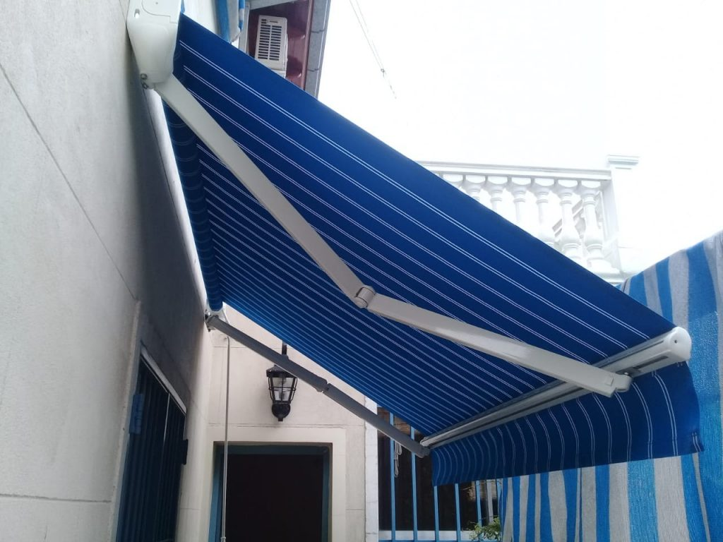 Toldo Brazos Invisibles con tela acrílica rayada azul y blanco